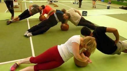 Fitnessübungen im Team mit Ball